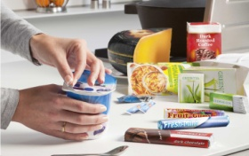someone opening a yogurt with packaged food products on a countertop in the background