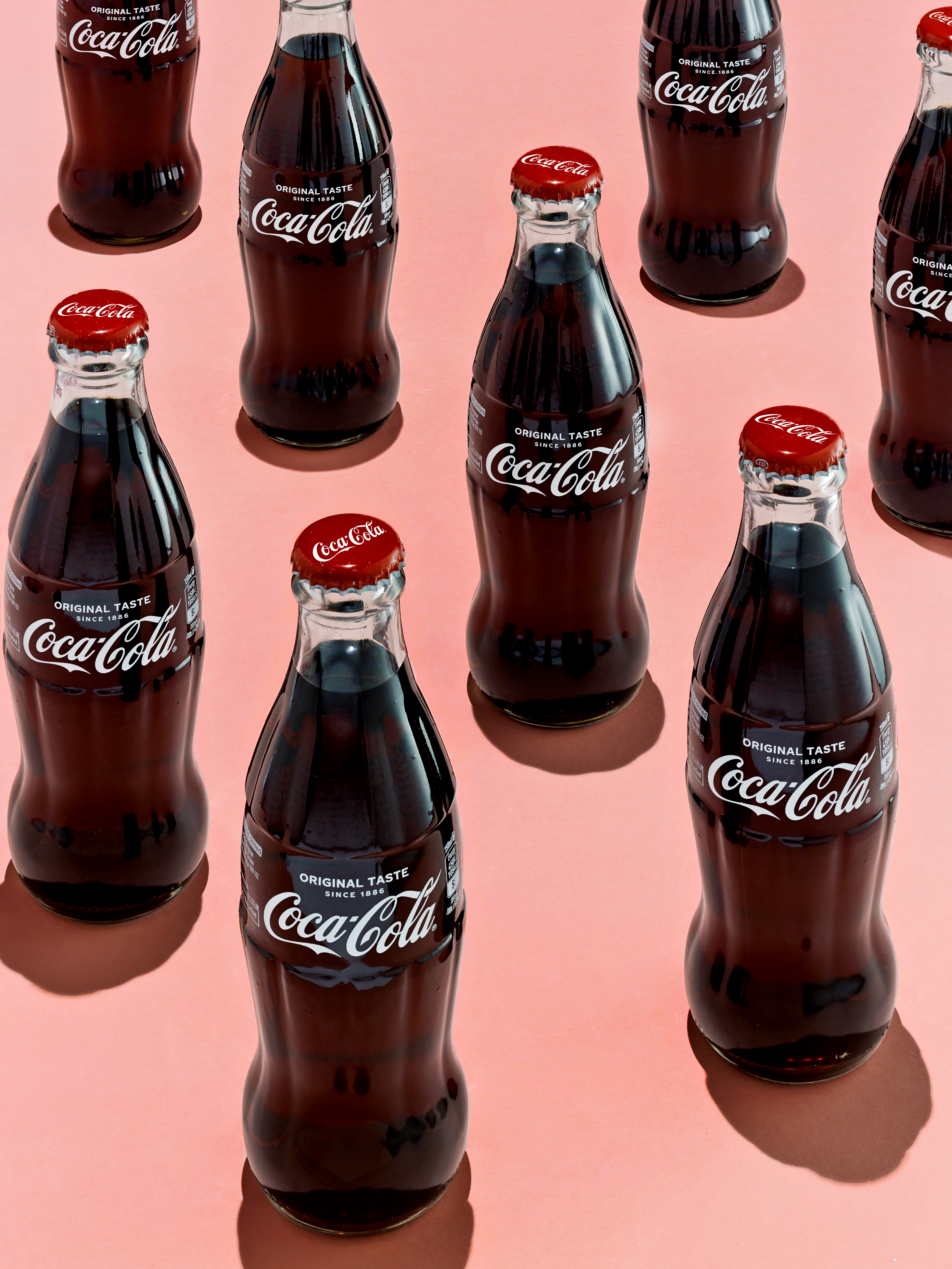 A close up of multiple glass Coca-Cola bottles showing their tactile design and iconic shape