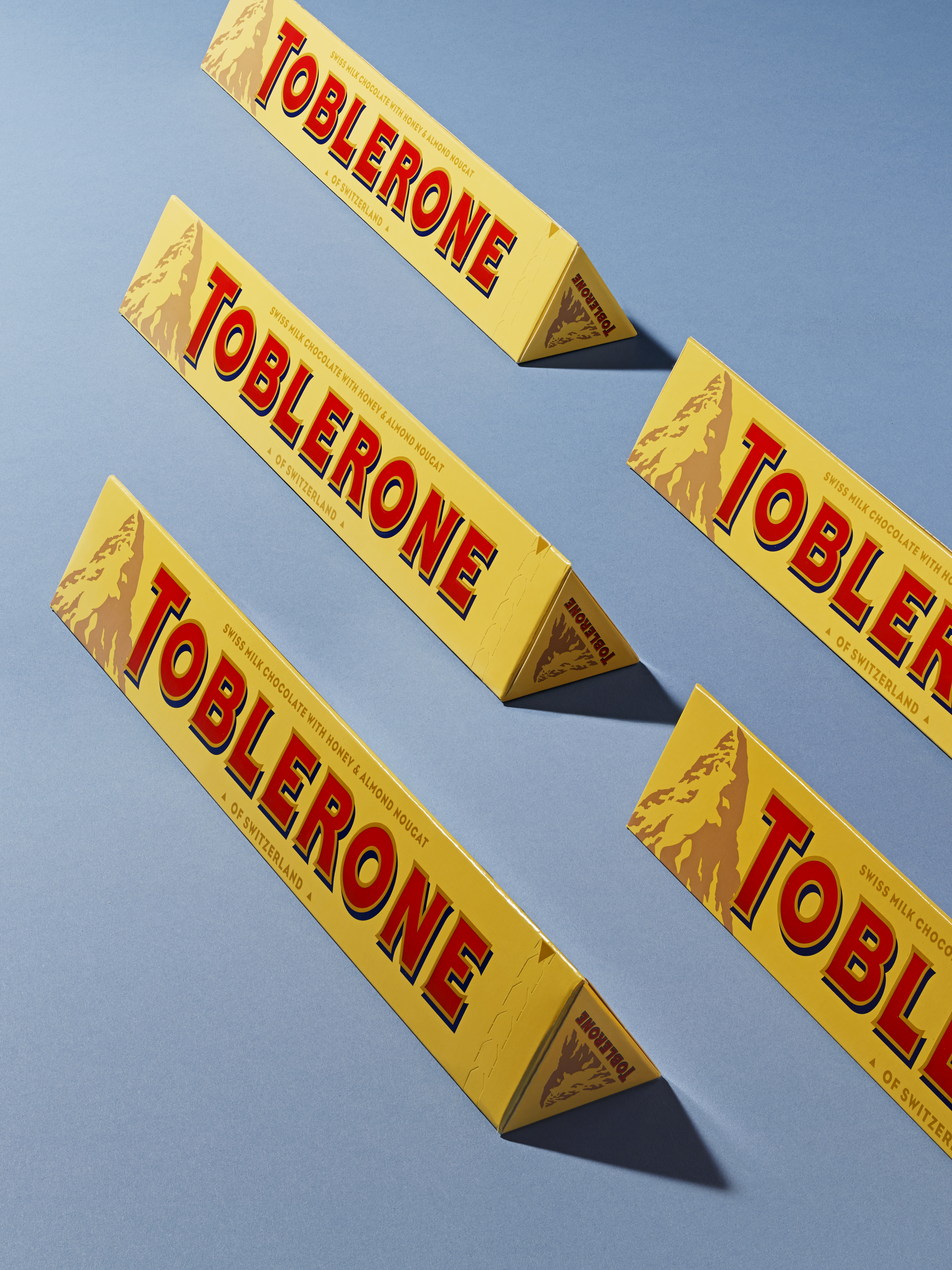 A close-up of multiple Toblerone bars showcasing their iconic triangular packaging